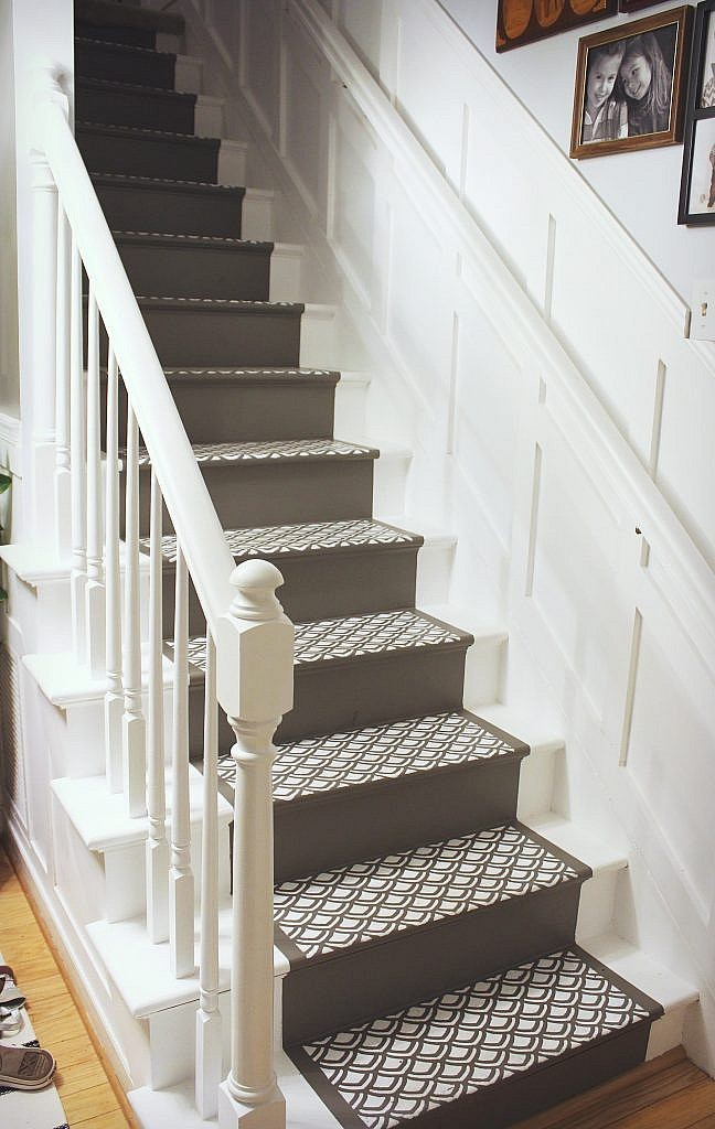 Stairs with painted runner, board and batten, and white railing